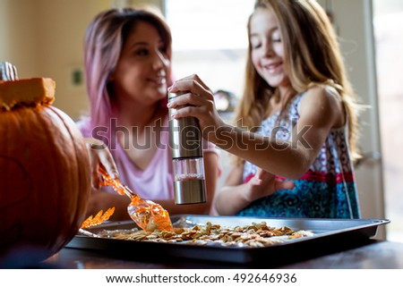 Mother and Daughter preparing Pumpkin seeds to bake