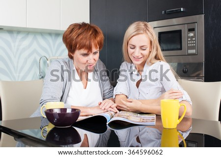 Mother and daughter read magazine at home. Happy women on the kitchen - stock photo