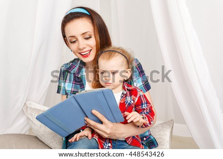 Mother and daughter read the e-book. Young mother and baby daughter hugging sitting on the floor. Girls dressed in plaid shirt. Family education - stock photo
