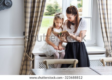 Mother and daughter reading a book - stock photo