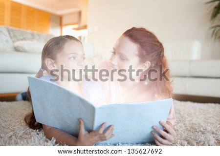 Mother and daughter reading a magical story together on a carpet - stock photo