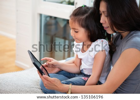 Mother and daughter reading electronic book at home - stock photo