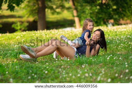 Mother and daughter relaxing and having fun in park on a beautiful summer day