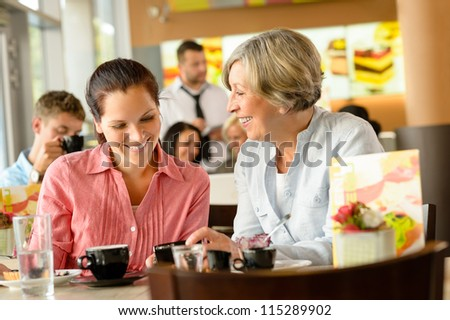 Mother and daughter relaxing in a cafe women restaurant happy - stock photo