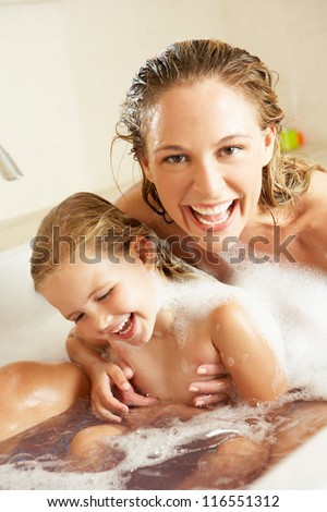Mother And Daughter Relaxing In Bubble Filled Bath - stock photo
