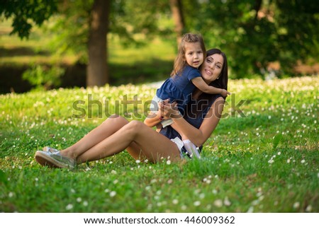 Mother and daughter relaxing in park on a beautiful summer day
