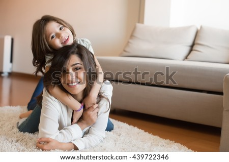 Mother and daughter relaxing together at home - stock photo
