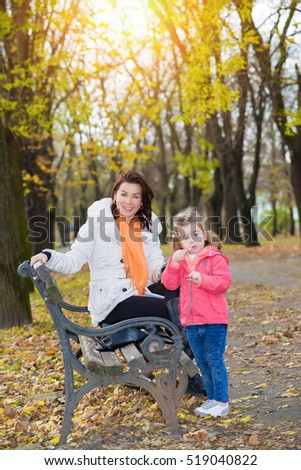 Mother and daughter resting in the autumn park.Little girl applying lips balm.Focus on the woman face