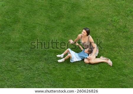 Mother and daughter resting on green lawn - stock photo