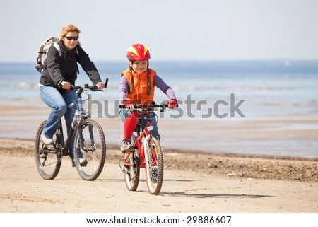 Mother and daughter riding on bicycles along beach
