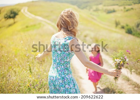 Mother and daughter running towards each other - stock photo