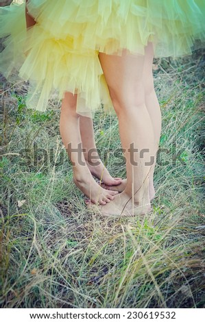 Mother and daughter's feet on the grass - stock photo