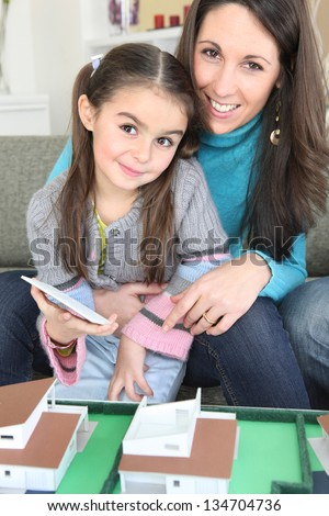 Mother and daughter sat by scale model of housing - stock photo