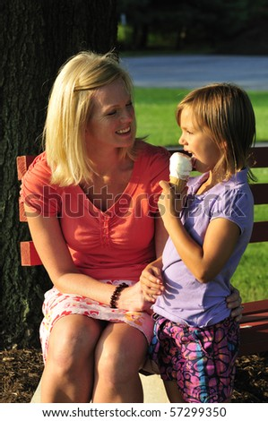 mother and daughter sharing ice cream in the park - stock photo