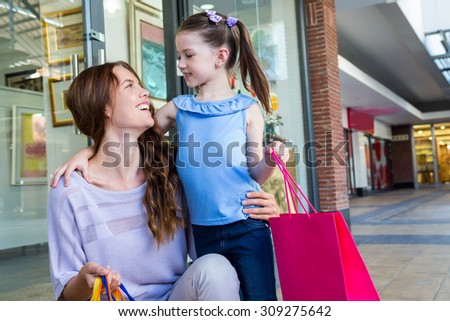 Mother and daughter shopping at the mall on a sunny day - stock photo