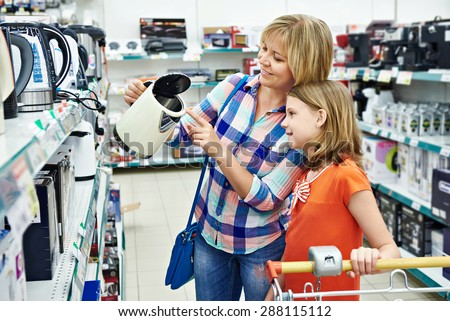 Mother and daughter shopping for electric kettle, smiling - stock photo