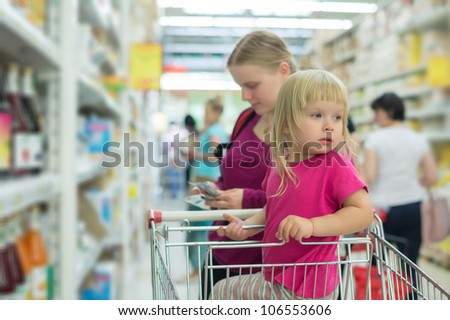 Mother and daughter shopping in juice section in supermarket - stock photo