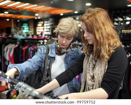 Mother and daughter shopping in textile store, real people and available light selective focus on older woman - stock photo