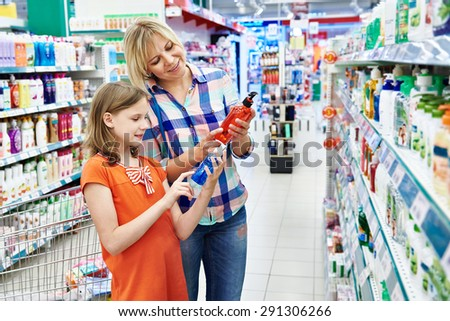 Mother and daughter shopping shampoo in supermarket