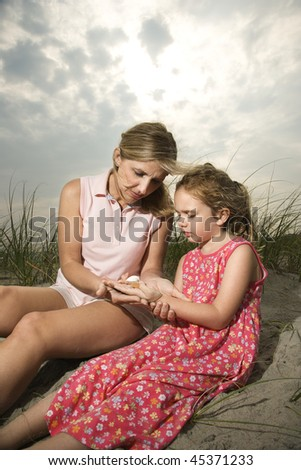 Mother and daughter sit on sand looking at seashells together. Vertical shot. - stock photo
