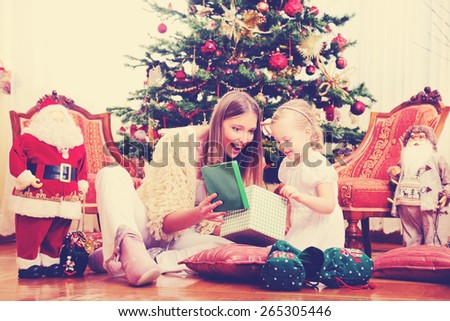 Mother and daughter sitting in front of the Christmas tree,shallow depth of field - stock photo