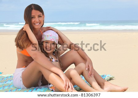 Mother and daughter sitting on a beach - stock photo