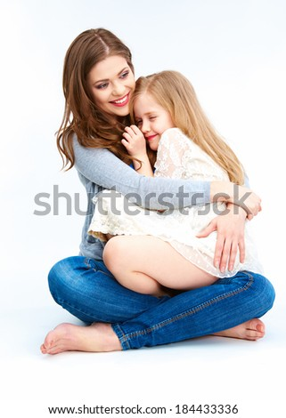 Mother and daughter sitting on a floor. Isolated on white background. - stock photo