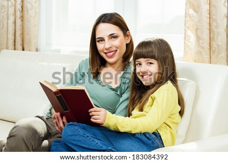 Mother and daughter sitting on sofa at their home and reading a book together,Leisure time for mother and daughter - stock photo