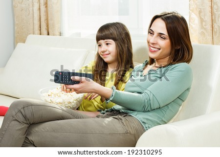 Mother and daughter sitting on sofa at their home,eating popcorn and watching tv,Family time