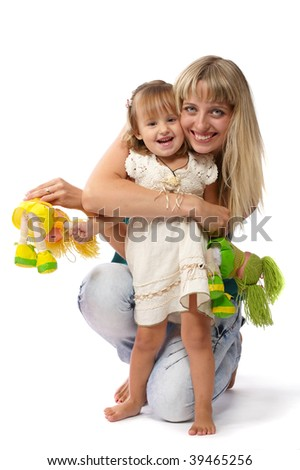 Mother and daughter sitting on the floor and play with toys