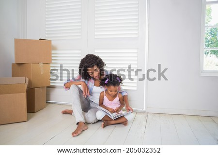 Mother and daughter sitting on the floor reading storybook in their new home - stock photo