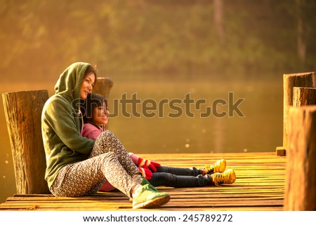 Mother and daughter sitting on the wooden bridge near the river - stock photo