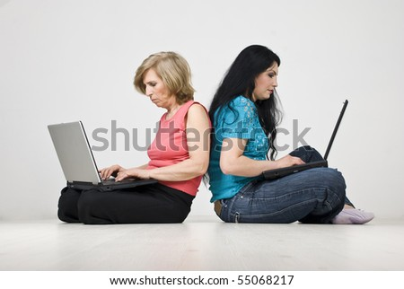 Mother and daughter sitting on wooden floor back to back and working on laptops in their home
