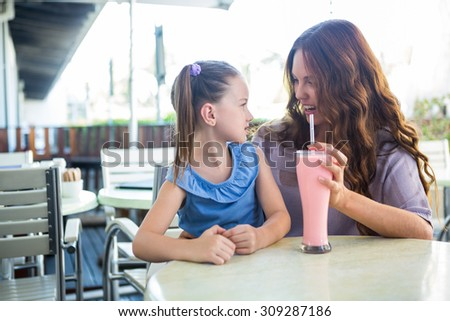 Mother and daughter sitting outside the cafe on a sunny day - stock photo