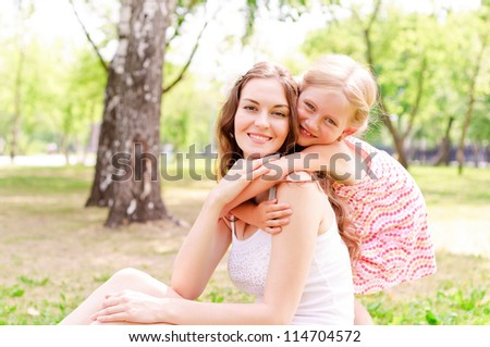 mother and daughter sitting together on the grass, and spend time with family