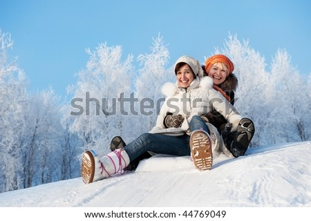 Mother and daughter sliding in the snow - stock photo