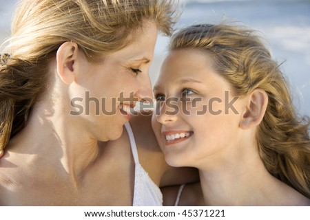 Mother and daughter smile while looking into one another's eyes. Horizontal shot. - stock photo