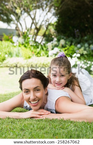 Mother and daughter smiling at camera outside in the garden