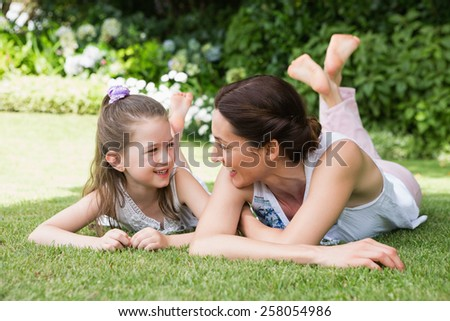 Mother and daughter smiling at each other outside in the garden - stock photo