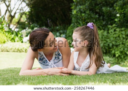 Mother and daughter smiling at each other outside in the garden