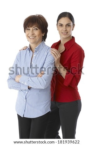 Mother and daughter smiling happy, looking at camera. Daughter touching senior mother's shoulders. - stock photo