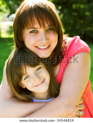 Mother and daughter smiling outdoor. - stock photo