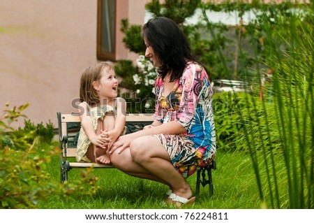 Mother and daughter spending time together in garden - family house in background