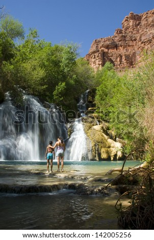 Mother and Daughter standing in front of Navajo Falls on Havasu Creek, Arizona. - stock photo