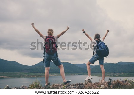 Mother and daughter  standing near the lake at the day time.  Concept of friendly family. - stock photo