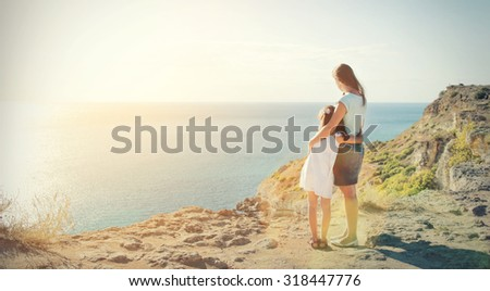 Mother and daughter standing on the edge of the mountain and look at the sea - stock photo