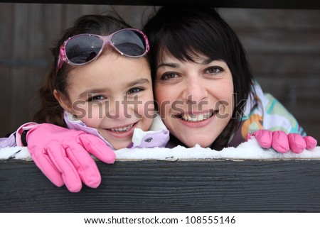 Mother and daughter stood by their ski house - stock photo