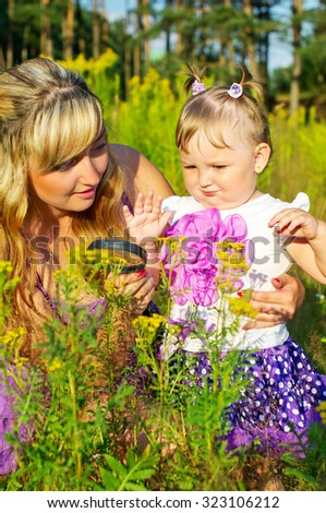 Mother and daughter studying nature under a magnifying glass - stock photo