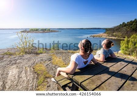 Mother and daughter sunbathing on Swedish coast - stock photo