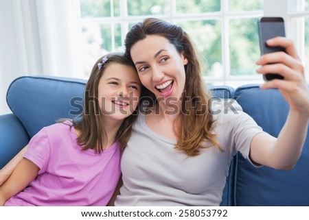 Mother and daughter taking a selfie at home in the living room - stock photo